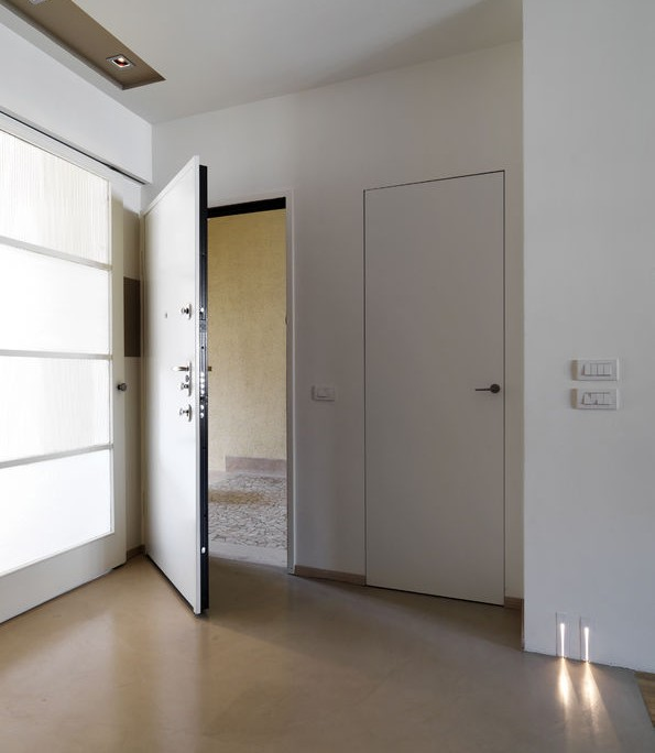 55813107 - interior view of a modern entrance of apartment with white main door and resin floor